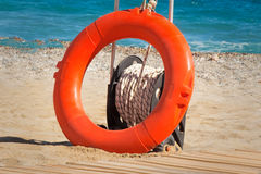 Lifebuoy at water on the coast of a sea beach. Royalty Free Stock Photos