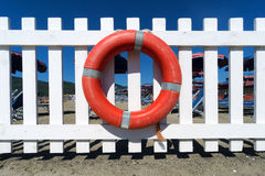 Lifebuoy on wooden fence. Lifebuoy attached to a white wooden fence Royalty Free Stock Photos