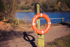 Lifebuoy on wooden post in park Royalty Free Stock Photos