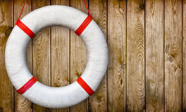 Lifebuoy on a wooden wall. White lifebuoy on a wooden wall royalty free stock photography