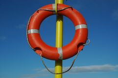 Lifebuoy on a yellow pillar. In front of blue sky Royalty Free Stock Photos