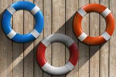 Lifebuoys на деревянной стене с песком Стоковое Изображение