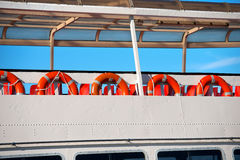 Lifebuoys in a Ferry Boat. A row of red and orange life buoys on the deck of a passenger ship Stock Images