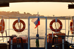 Lifebuoys and Russian flag on board the ship on sunset background.  Royalty Free Stock Image