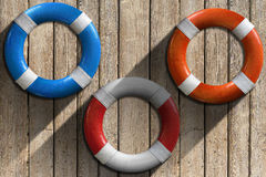 Lifebuoys on Wooden Wall with Sand Stock Image
