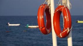 Lifebuoys zrozumienie na molu w dennym kiwaniu na falach łódź zbiory wideo