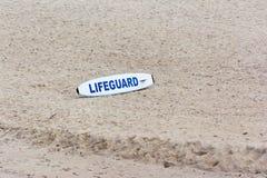 Lifegourd冲浪板坐海滩 图库摄影