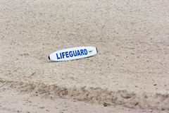 Lifegourd surfboard sitting on beach. White surfboard with lifeguard text sitting on sandy beach Stock Photography