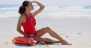 Lifeguard με το χέρι που ψάχνει πλησίον brow τις διασώσεις απόθεμα βίντεο