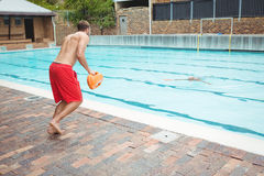 Lifeguard που πηδά σε μια πισίνα στη διάσωση που πνίγει το ανώτερο άτομο Στοκ Εικόνα