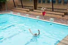 Lifeguard που πηδά σε μια πισίνα στη διάσωση που πνίγει το ανώτερο άτομο Στοκ φωτογραφίες με δικαίωμα ελεύθερης χρήσης