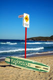 Lifeguard. Abandoned lifeguard surf, sign 'dangerous current', on blue clear sky Royalty Free Stock Photos