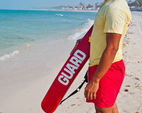 The Lifeguard. A lifequard stands on the beach, watching for swimmers in danger Royalty Free Stock Images