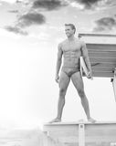 Lifeguard. Young fit lifeguard on duty at the beach standing on tower Royalty Free Stock Photo