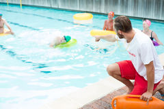 Lifeguard assisting swimmers at poolside Stock Photo