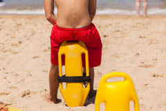 Lifeguard Beach Rescue Bouy. Lifeguard rear undentified sitting with safety rescue swimming bouy Royalty Free Stock Image