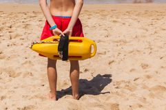 Lifeguard Beach Rescue Bouy. Lifeguard rear unidentified standing with safety rescue swimming bouy Stock Photos