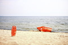 Lifeguard beach rescue equipment. Beach life-saving. Lifeguard rescue equipment orange preserver tool and boat, red plastic buoyancy aid in the sand Stock Photos