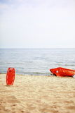Lifeguard beach rescue equipment. Beach life-saving. Lifeguard rescue equipment orange preserver tool and boat, red plastic buoyancy aid in the sand Royalty Free Stock Photo