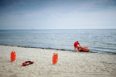 Lifeguard beach rescue equipment. Beach life-saving. Lifeguard rescue equipment orange preserver tool and boat, red plastic buoyancy aid in the sand Stock Image