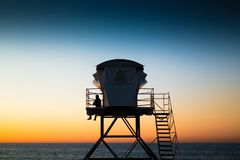 A lifeguard at the beach on the watchtower at sunset royalty free stock images