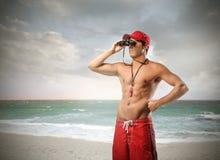 Lifeguard with binoculars. A sexy lifeguard at the beach is using binoculars Stock Photography