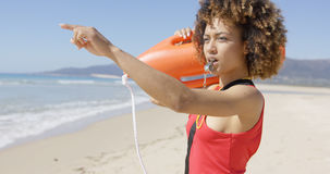 Lifeguard blowing a whistle on beach Stock Image