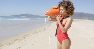 Lifeguard blowing a whistle holding rescue float. Lifeguard female wearing red swimsuit blowing a whistle holding rescue float. Tarifa beach. Provincia Cadiz Stock Photo