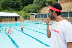 Lifeguard blowing whistle while students playing in pool. On a sunny day Stock Image