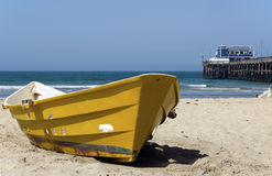 Lifeguard Boat. A yellow lifeguard boat sits on the sand.  A pier is in the background Stock Photography