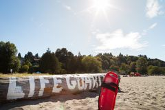 A lifeguard buoy in the sand in front of a log with lifeguard written on it. royalty free stock photo