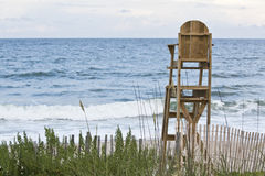 Lifeguard Chair. A wooden lifeguard chair on a deserted beach with ocean, sanddune fencing and seaoats g royalty free stock image
