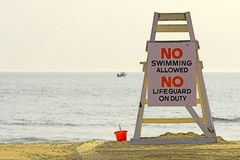 Lifeguard chair. With sign saying no swimming royalty free stock image