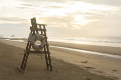 Lifeguard chair on an empty beach. In warm cloudy morning light stock image