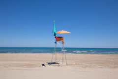 Lifeguard chair in lonely Pine Beach. Lifeguard high chair with orange parasol and green flag in Pine Beach, in Grao of Castellon, Valencia, Spain, Europe. Blue Royalty Free Stock Image