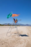 Lifeguard chair in Pine Beach. Lifeguard high chair with parasol and green flag in Pine Beach, in Grao of Castellon, Valencia, Spain, Europe. Blue clear sky Stock Photos