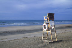 Lifeguard chair on stormy beach. Lifeguard chair on an emply stormy beach and overcast cloudy sky on a bad weather day royalty free stock image