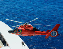 Lifeguard descend from helicopter. On ship at blue sea Stock Image