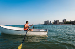 Lifeguard on Duty in the Beach. Lifeguard in boat with a city in the background looking at the beach full of people Stock Photos