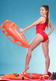Lifeguard on duty with rescue buoy supervising. Stock Photos