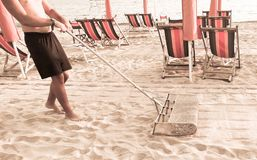 Lifeguard at the end of the day cleanse with sieve sand beach royalty free stock image