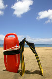 Lifeguard Equipment. Lifeguard float and flippers on bright beach Stock Photo
