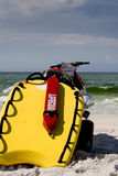 Lifeguard Equipment. Bright yellow lifesaving equipment attached to the back of a water craft and a red flotation device with the word lifeguard in white and the Royalty Free Stock Images