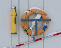 Lifeguard equipment hanging on marina wall. Lifeguard equipment hanging on white wooden marina wall royalty free stock image