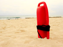 Lifeguard equipment. Typical red plastic lifeguard tube on a sandy beach in Mexico Royalty Free Stock Image