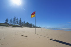 Lifeguard flag on Australian beach. Lifeguard flag on sunny Gold Coast beach with Surfers Paradise in the background, Australia Stock Image