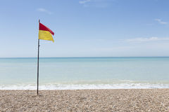 Lifeguard flag on an empty pebble beach on a bright sunny day Royalty Free Stock Image