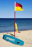 Lifeguard flag, surfboard and flotation device Royalty Free Stock Images