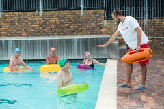 Lifeguard helping swimmers at poolside Stock Photos