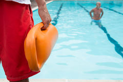 Lifeguard holding rescue buoy at poolside. Mid section of lifeguard holding rescue buoy at poolside Stock Image